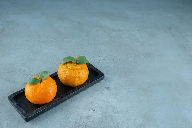 Świeże mandarynki na drewnianym talerzu, na marmurowym tle. zdjęcie wysokiej jakości