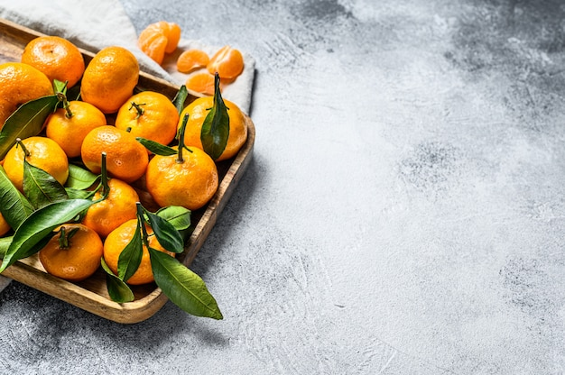 Świeże mandarynki owoc lub mandarynki z liśćmi w drewnianej misce.