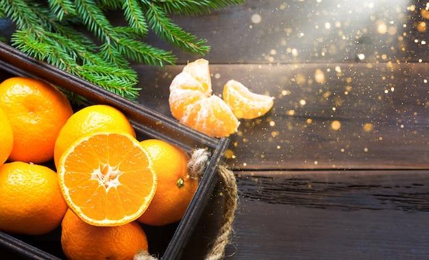 Świeże mandarynki w brązowym pudełku na drewnianym tle z zielonymi gałęziami jodły. rama, kopia przestrzeń, zapach wakacyjny i zimowy, nowy rok, boże narodzenie. zdrowa żywność, sok pomarańczowy, witryna sklepowa. pokrój i pokrój