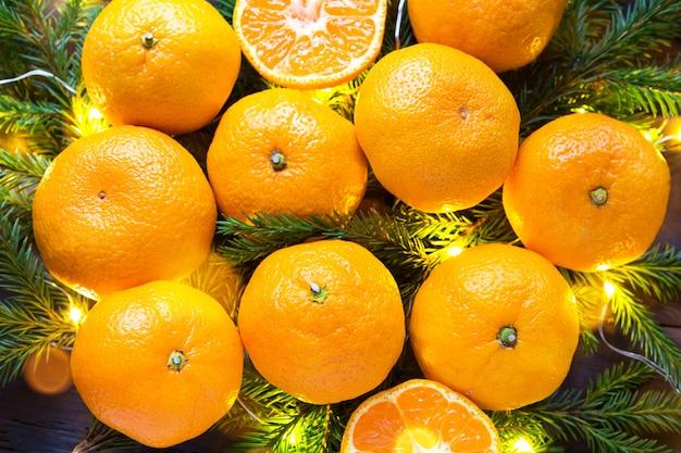 Świeże mandarynki w girlandach, na gałęziach jodły i blichtru - jasne tło nowego roku. połowa pomarańczowego, świątecznego cytrusowego aromatu. boże narodzenie, nowy rok. miejsce na tekst.