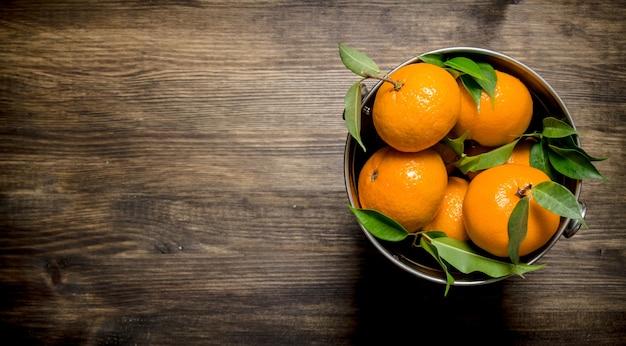 Świeże mandarynki w wiadrze z liśćmi na drewnianym stole. widok z góry