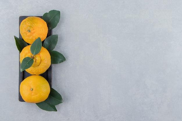 Świeże mandarynki z liśćmi na czarnym talerzu