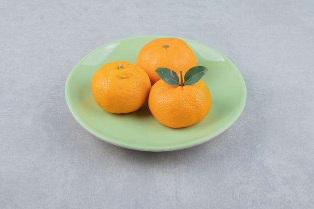 Świeże mandarynki z liśćmi na zielonym talerzu