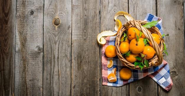 Świeże mandarynki z liśćmi w koszu na drewnianym stole. widok z góry