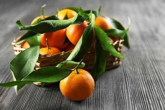 Świeże mandarynki z liśćmi w koszu na drewnianym stole, zbliżenie