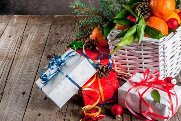 Świeże mandarynki z zielonymi liśćmi w białym koszu, ozdoby świąteczne i pudełka na prezenty