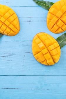 Świeże mango - piękne posiekane owoce z zielonymi liśćmi na jasnoniebieskim tle drewna