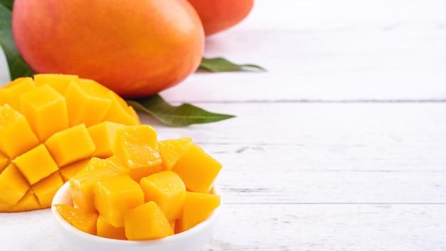 Świeże mango, piękne posiekane owoce z zielonymi liśćmi na jasnym tle drewniany stół