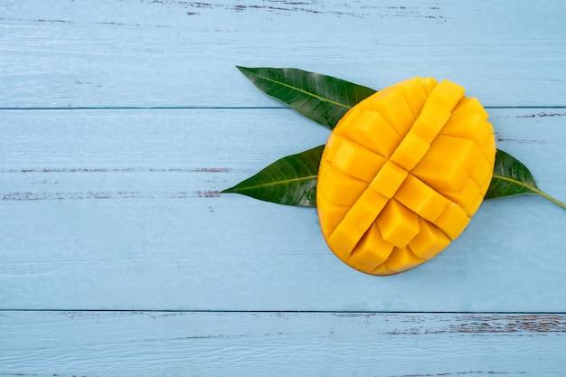 Świeże mango, piękne posiekane owoce z zielonymi liśćmi na tle ciemnego drewnianego stołu. koncepcja projektowania owoców tropikalnych. leżał płasko. widok z góry. skopiuj miejsce