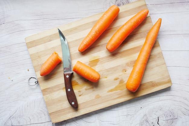 Świeże marchewki na desce do krojenia na stole