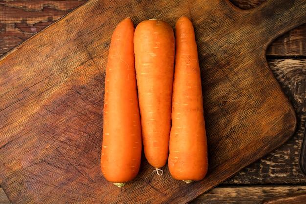 Świeże marchewki na drewnianej desce do krojenia. zobacz górę. skopiuj miejsce