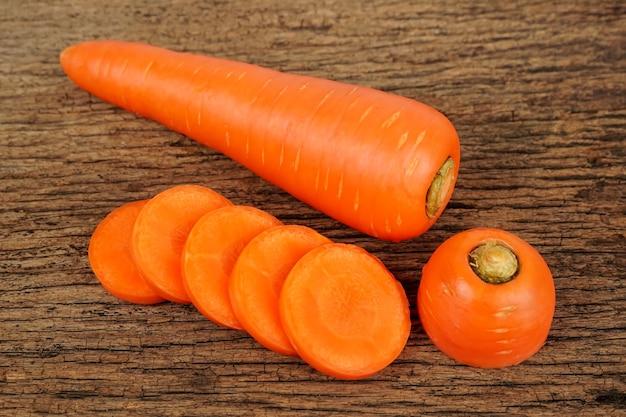 Świeże marchewki na drewnianym tle