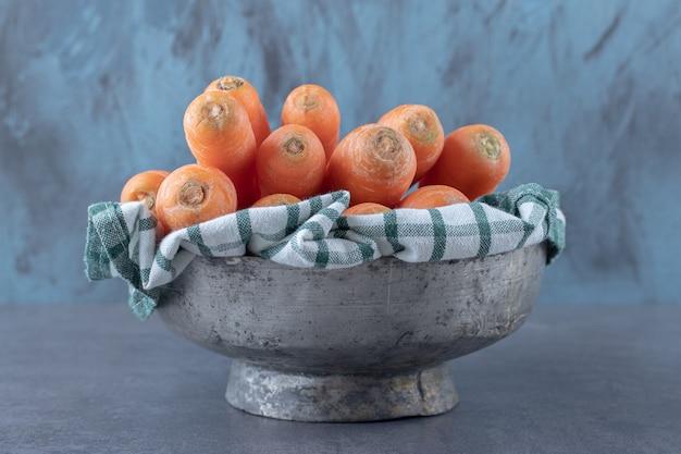Świeże marchewki na ręczniku w misce, na marmurowej powierzchni.