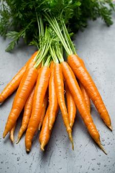 Świeże marchewki na szarym tle.