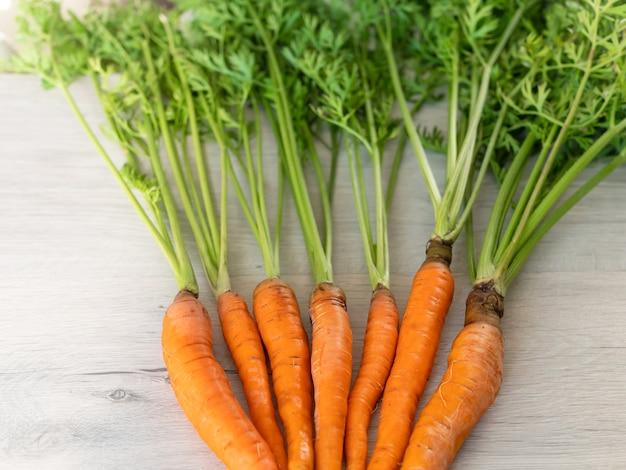 Świeże marchewki tylko z ogrodu. pomarańczowe marchewki z zieloną łodygą na jasnej powierzchni. apetyczne zdrowe warzywo.