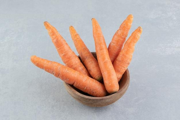 Świeże marchewki w misce, na marmurowym tle.