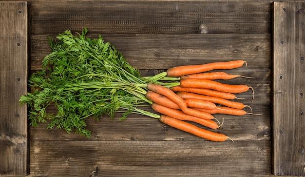 Świeże marchewki z zielonymi liśćmi na drewnianym tle. koncepcja żywności ekologicznej