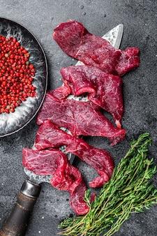 Świeże, marmurkowe mięso wołowe pokrojone w cienkie paski na gulasz. czarne tło. widok z góry.