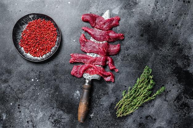 Świeże, marmurkowe mięso wołowe pokrojone w cienkie paski na gulasz
