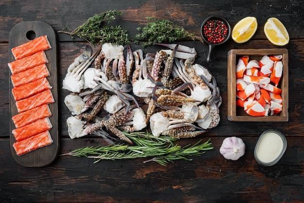 Świeże mięso kraba i paluszki surimi z niebieskim zestawem krabów pływackich, na ciemnym drewnianym tle, płaski widok z góry