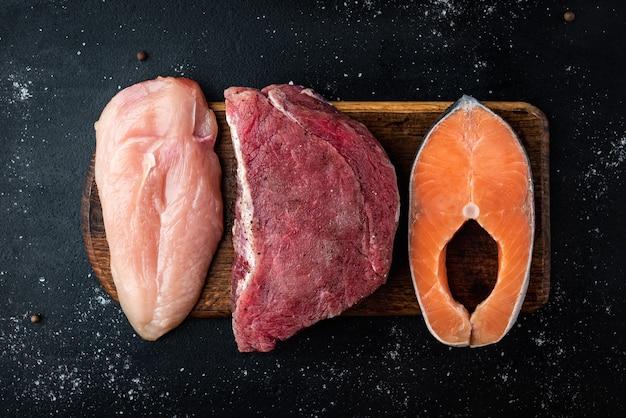 Świeże mięso, łosoś i filet z kurczaka na drewnianej desce do krojenia na czarnym tle. naturalna żywność o wysokiej zawartości białka. widok z góry.
