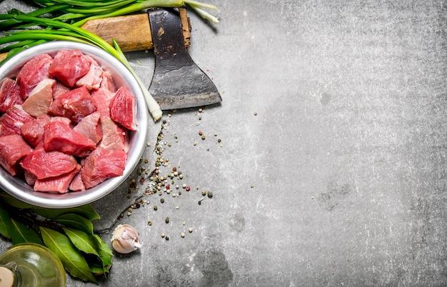 Świeże mięso posiekane siekierą i przyprawami. na kamiennym stole. wolne miejsce na tekst. widok z góry
