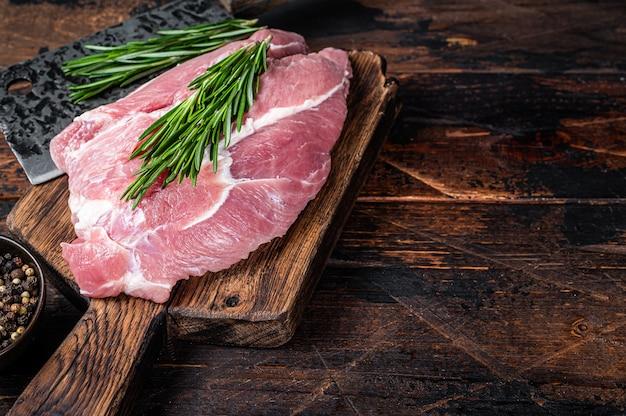 Świeże mięso surowe łopatki wieprzowe pokroić ze składnikami i przyprawami na tle kuchni. ciemne drewniane tło. widok z góry. skopiuj miejsce.