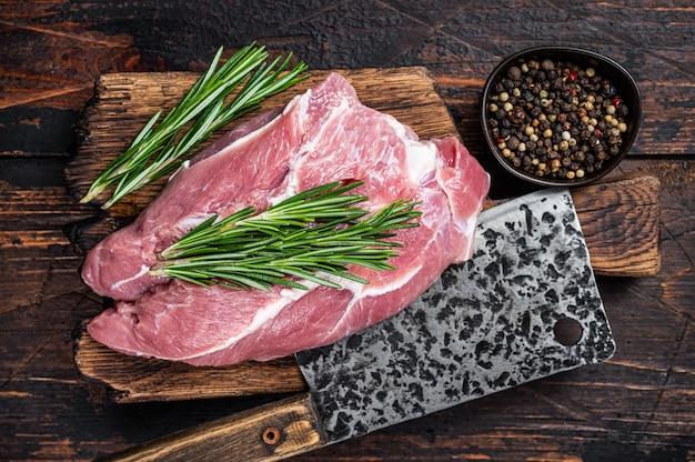Świeże mięso surowe łopatki wieprzowe pokroić ze składnikami i przyprawami na tle kuchni. ciemne drewniane tło. widok z góry.