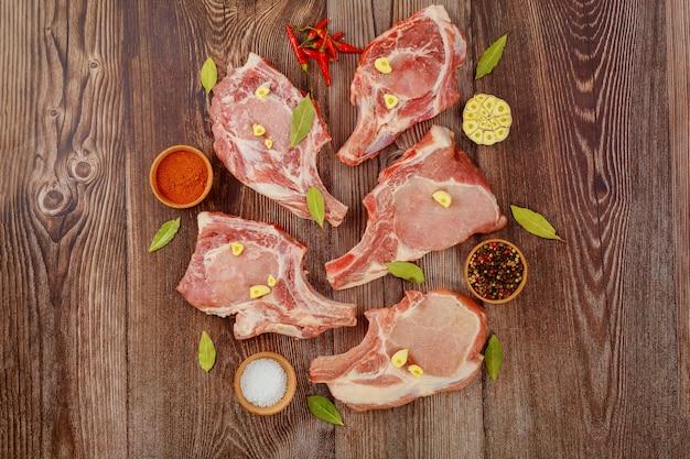 Świeże mięso wieprzowe w kości na drewnianym tle z przyprawami.