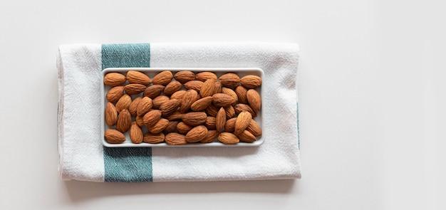 Świeże migdały orzechowe w ceramicznej misce z ręcznikiem
