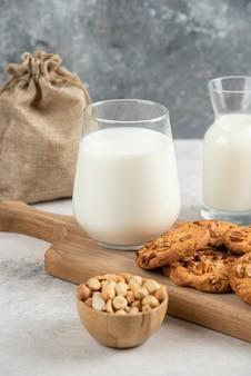 Świeże mleko i ciastka na drewnianej desce do krojenia z orzeszkami ziemnymi.