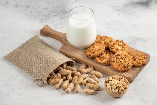 Świeże mleko i ciastka na drewnianej desce do krojenia z worem z orzeszków ziemnych.