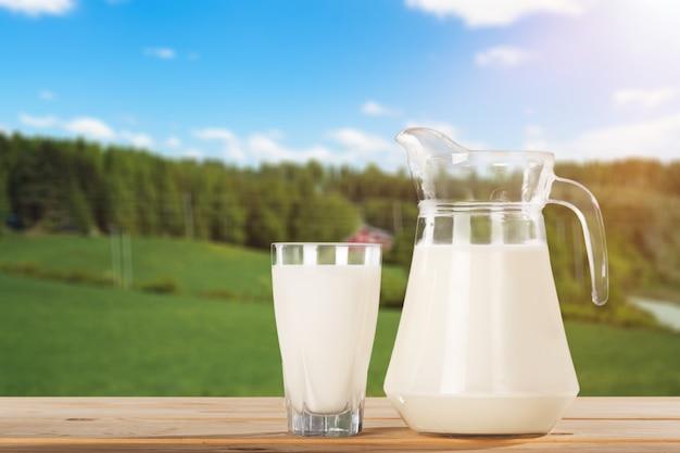 Świeże mleko krowie w szklance i dzbanku na drewnianym stole