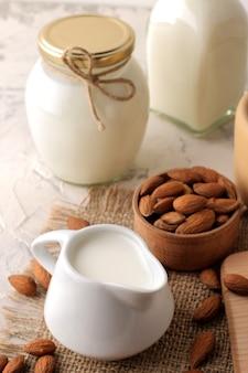 Świeże mleko migdałowe w mlecznym dzbanku i orzechy migdałowe na jasnym tle