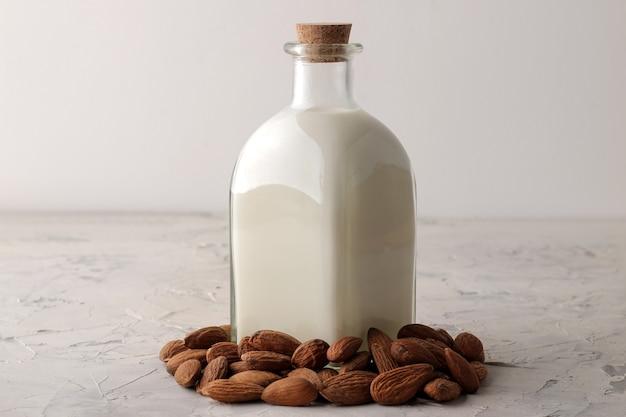Świeże mleko migdałowe w szklanej butelce i orzechy migdałowe na jasnym tle