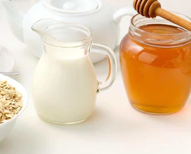 Świeże mleko w przezroczystej szklanej karafce i słoik miodu stoją na białym stole, zdrowy produkt, śniadanie