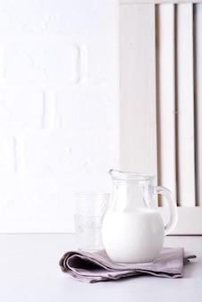 Świeże mleko w szklanym dzbanku i szklance