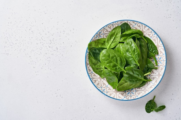 Świeże młode liście szpinaku w ceramicznej pięknej misce na jasnoszarym betonowym tle.