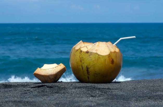Świeże młode owoce kokosa na ciemnej, piaszczystej plaży na południu wyspy jawa w indonezji, wybrane ognisko z rozmytym oceanem indyjskim w tle