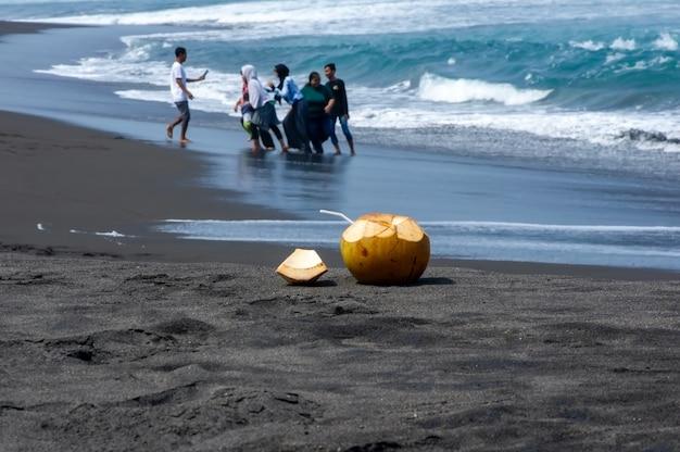 Świeże młode owoce kokosowe na ciemnej, piaszczystej plaży w pantai dewa ruci purworejo, indonezja, wybrane skupienie z rozmytymi ludźmi robiącymi zdjęcia w tle