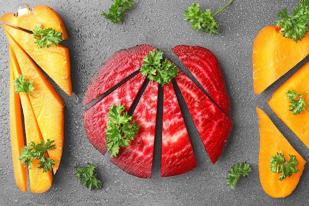 Świeże młode pokrojone buraki i marchewki z pietruszką na szarym tle