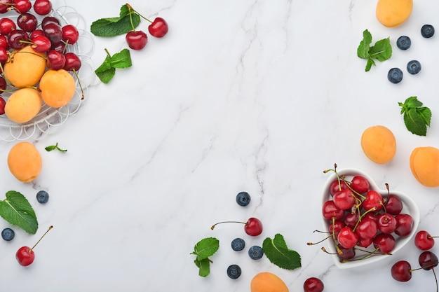 Świeże morele, czerwona wiśnia i jeżyna na białym tle marmuru. wegetariańskie, odchudzanie, koncepcja czystego i zdrowego jedzenia. widok z góry. skopiuj miejsce.
