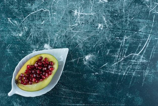Świeże nasiona granatu wewnątrz owocu mango.
