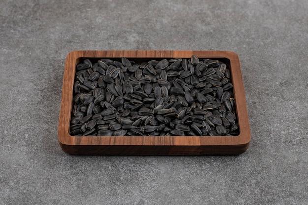 Świeże nasiona słonecznika w drewnianej misce.