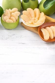 Świeże obrane pomelo, pummelo, grejpfrut, shaddock na jasnym drewnianym stole tle. owoce sezonowe na święto środka jesieni, z bliska, kopia przestrzeń.