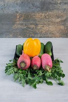 Świeże ogórki, czerwona rzodkiewka i pieprz na kamiennym stole. wysokiej jakości zdjęcie