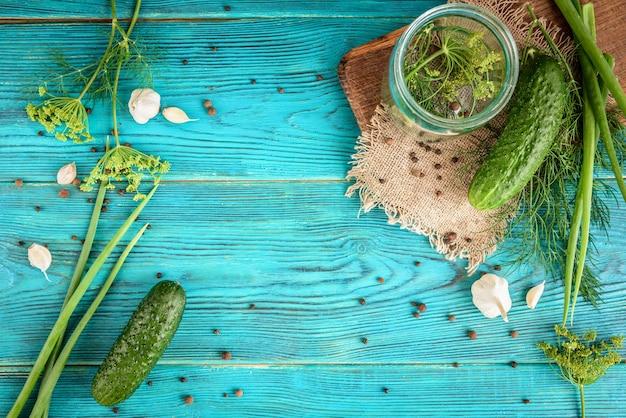 Świeże ogórki gotowe do konserw z koperkiem, czosnkiem i przyprawami na niebieskim drewnie