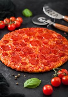 Świeże okrągłe pieczone gorące i pikantne pizzy pepperoni z nożem kołowym i nożem z pomidorami i bazylią na tle czarnego stołu kuchennego.