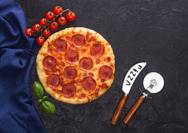 Świeże okrągłe pieczone włoska pizza pepperoni z nożem do kół i nożem z pomidorami i bazylią na tle czarnego stołu kuchennego.