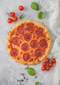 Świeże okrągłe pieczone włoska pizza pepperoni z pomidorami z bazylią na tle jasnego stołu kuchennego. miejsce na tekst